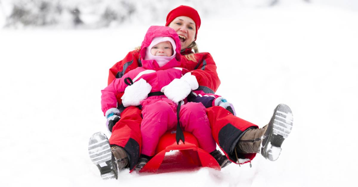mother and daughter sledding together