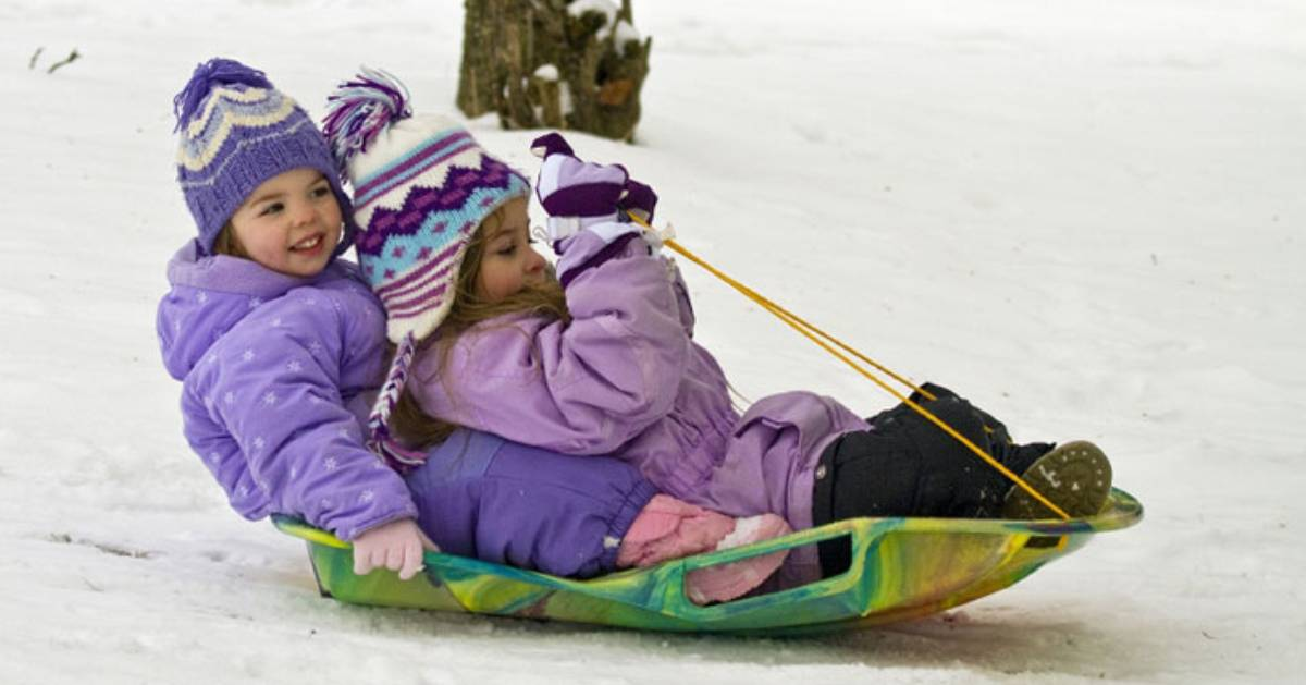 young kids sledding down a hill