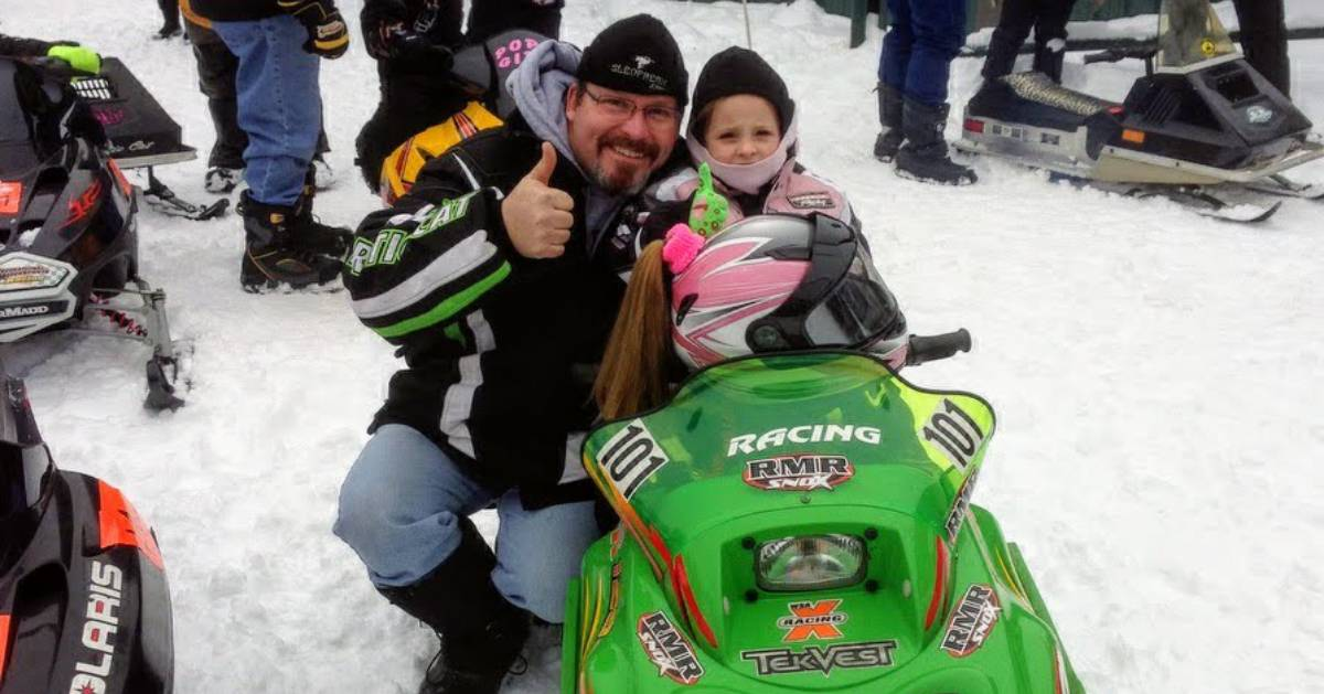 young girl in snowmobile with grandfather