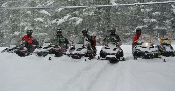 a line of snowmobilers
