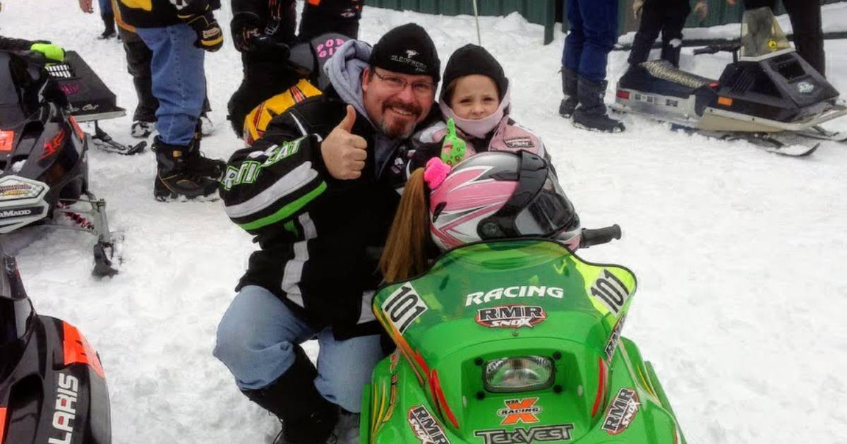 man with kid in snowmobile