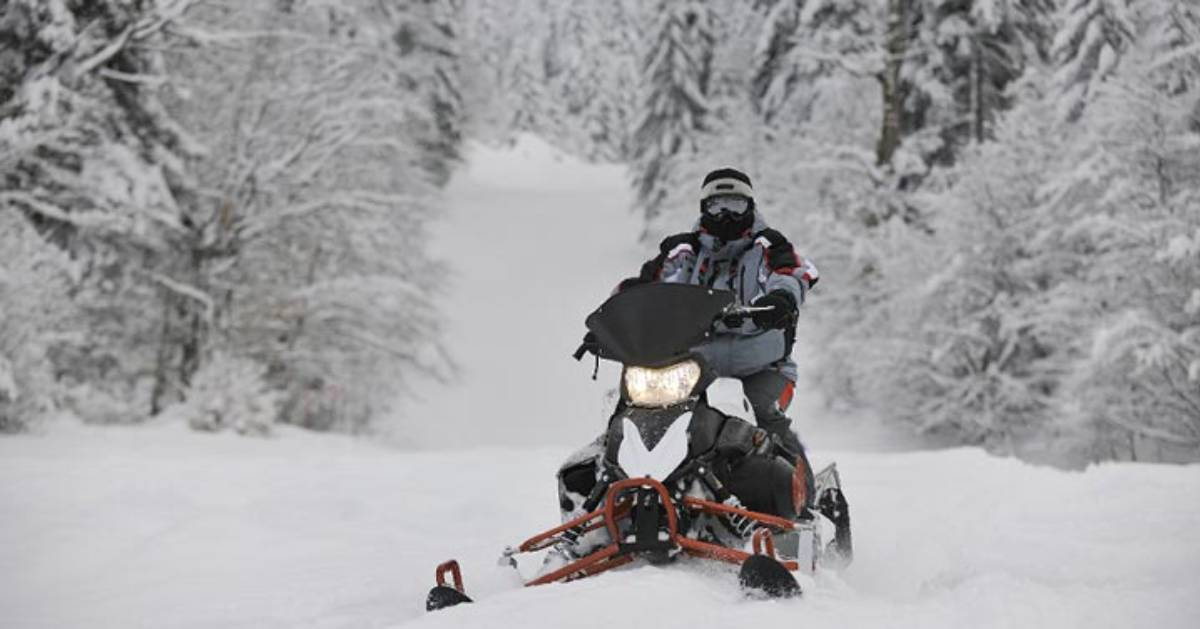 snowmobiler riding through snow