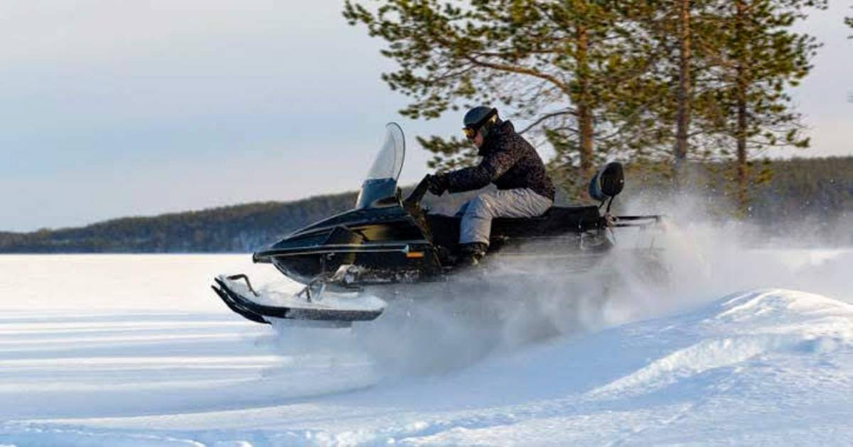 a snowmobiler riding fast