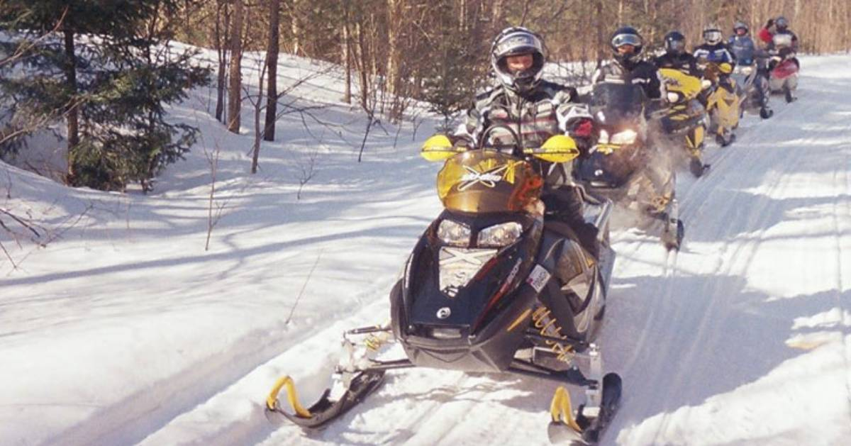group of snowmobile riders in a row