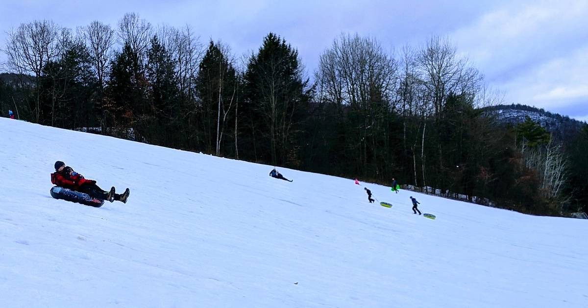 people going down a snow tubing hill