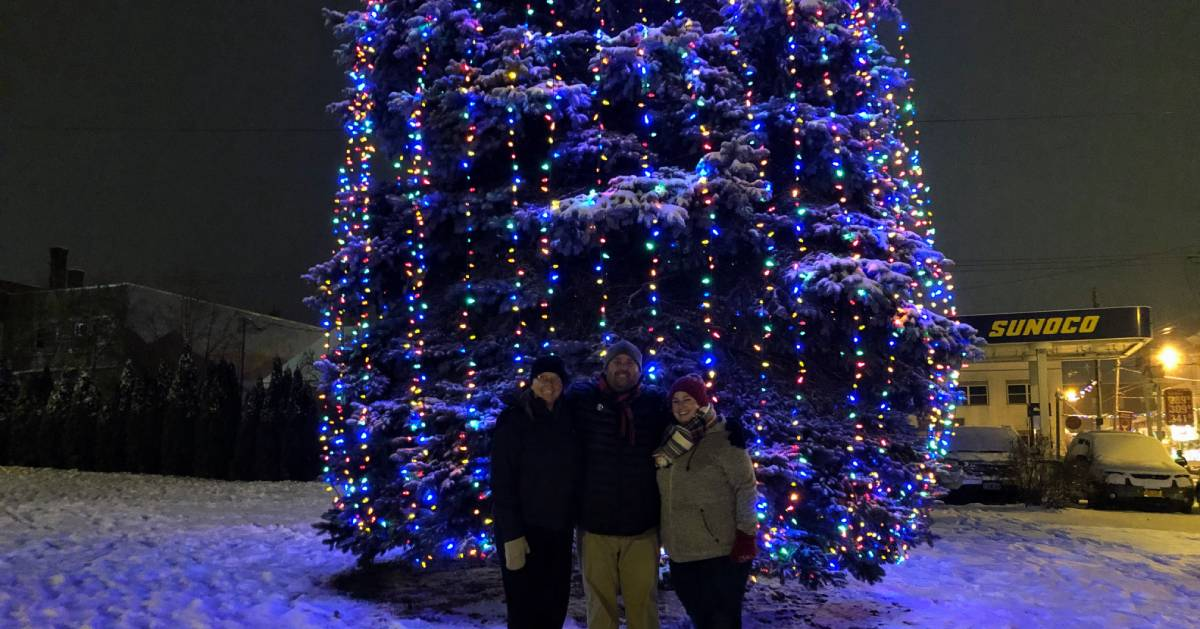 three people posing in front of giant lit tree