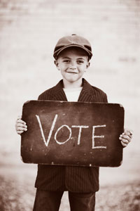 young boy in newsboy cap and suit jacket holding sign that reads 'vote'