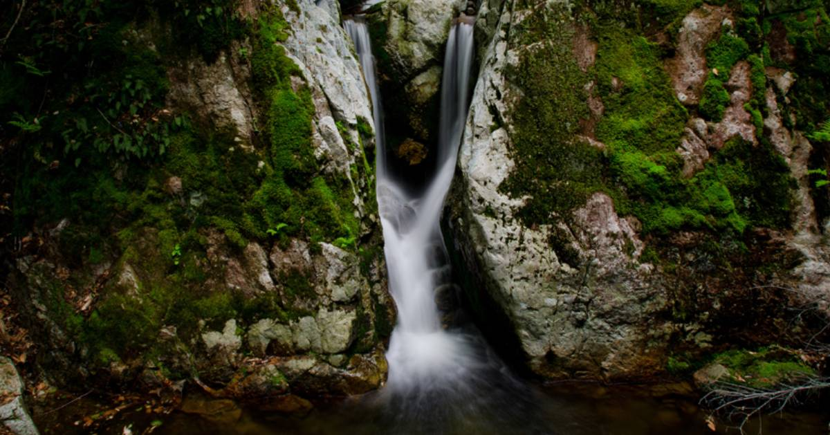 waterfall that looks like it's being split in two by a large boulder