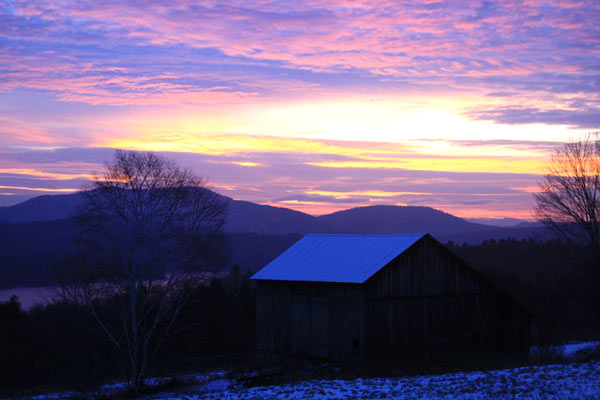 Barn overlooking mountains during sunrise