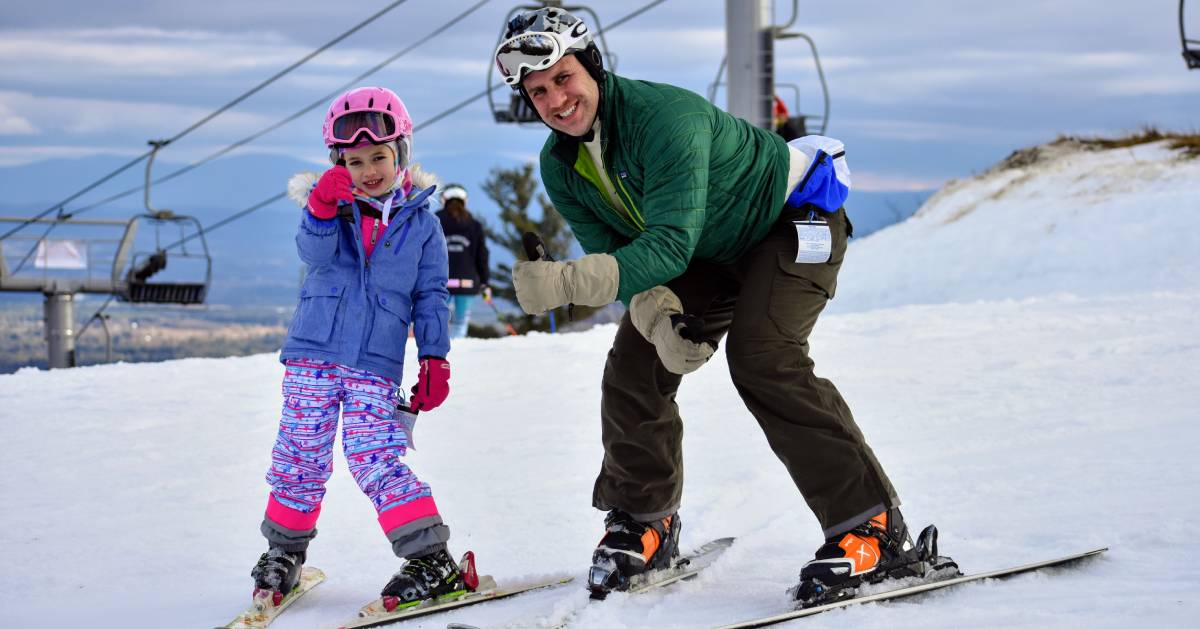 dad and daughter posing to ski