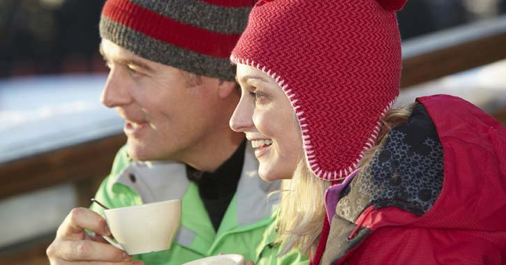 people in winter clothes holding warm drinks