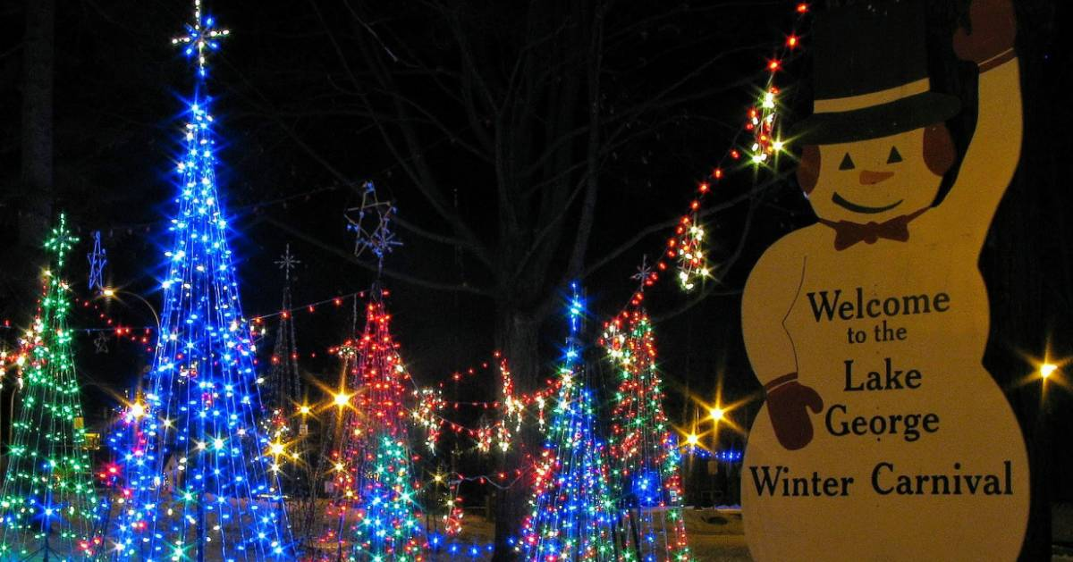 lit up fake trees by Lake George Winter Carnival sign