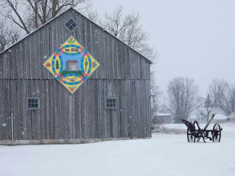 Colorful painted barn quilt displayed on a grey barn in winter in Hammond NY