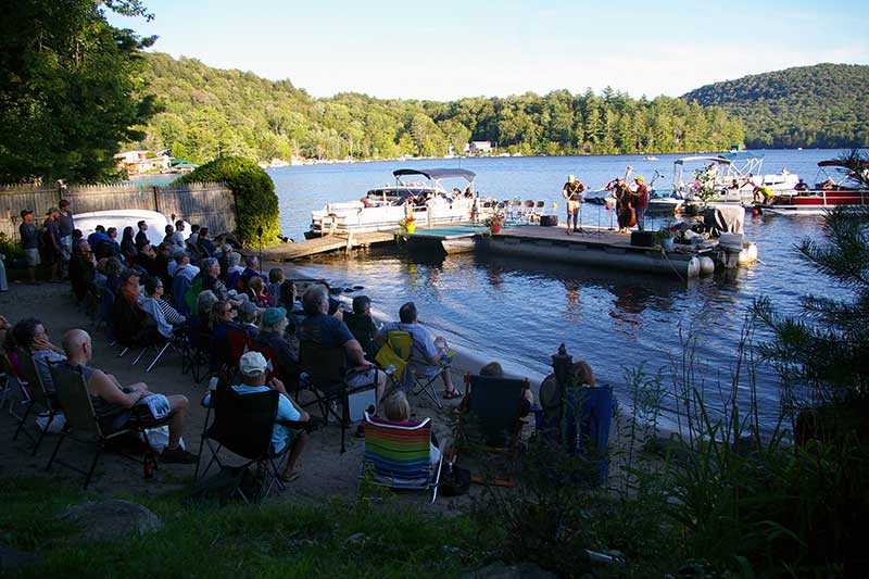 Musicians play from a dock on Caroga Lake during the Caroga Lake Music Festival