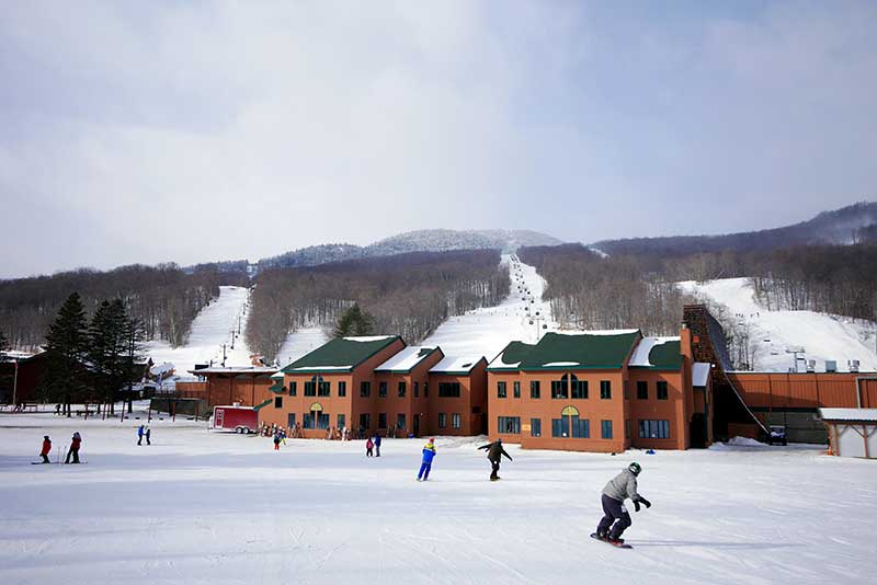 Skiiers and snowboarders descend Gore Mountain