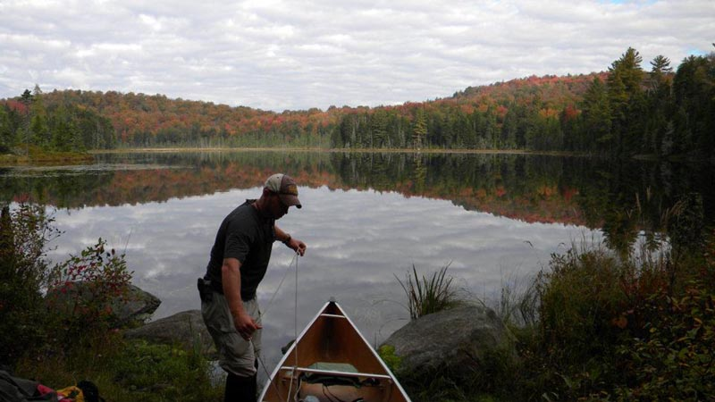 Man loading a canoe into a pond near Olmstedville NY