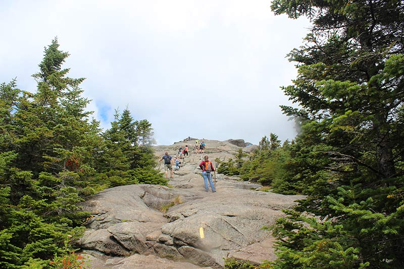 A steep rock incline with people walking up to summit