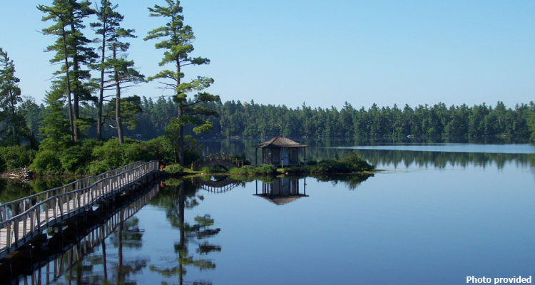 small wooden structure at white pine camp surrounded by water
