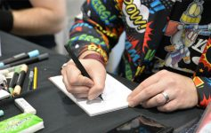 close up of Comic Con person signing an autograph
