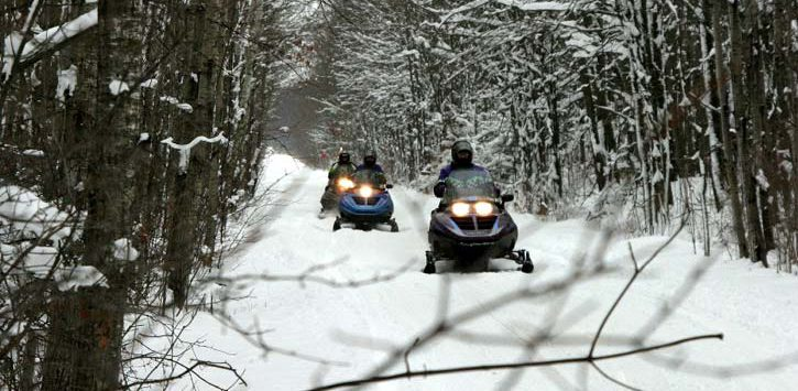 riders on snowmobiles on trail