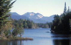 a large pond below a mountain
