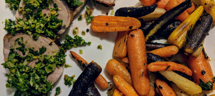 pork with kale pesto and rainbow colored carrots