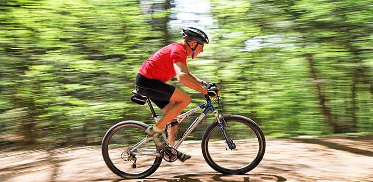 man bikes through forest