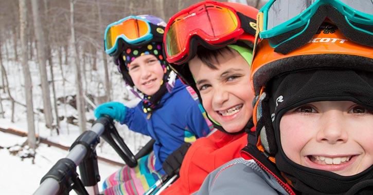three kids in ski gear