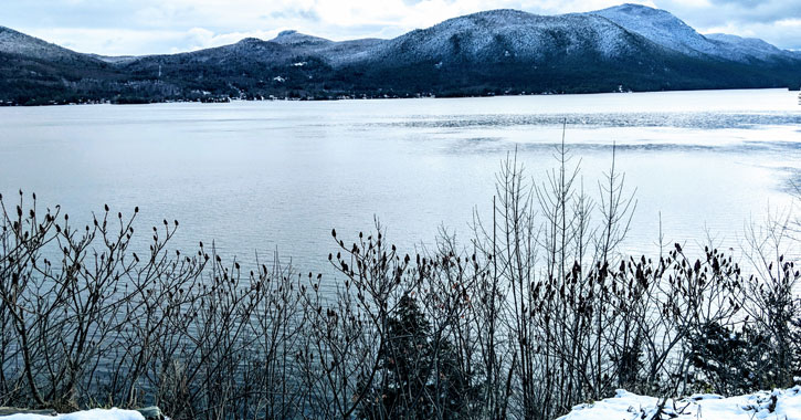 view of mountain and water in the winter