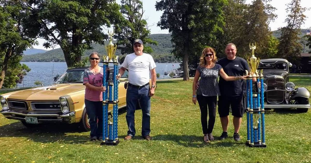 people standing by cars with trophies