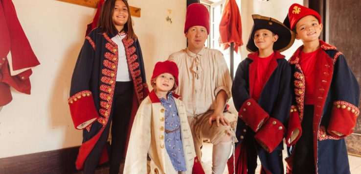 kids dressed in colonial uniforms with a costumed interpreter at fort ticonderoga