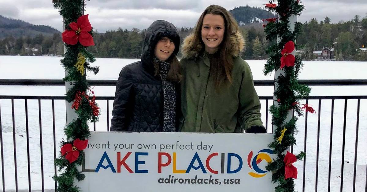 two women posing by Lake Placid sign in winter