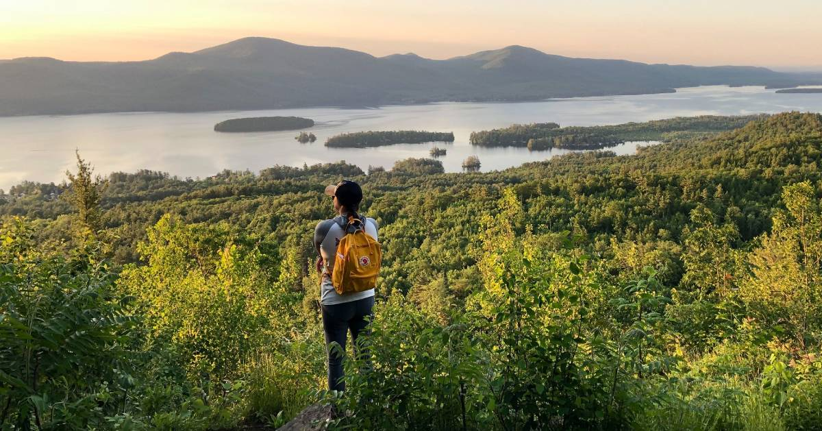 woman hiking looks out at summit