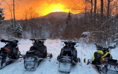 snowmobiles at sunset