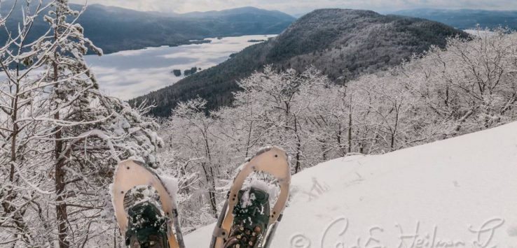 snowshoed feet looking out over winter summit scene