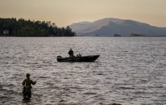 anglers in lake, one in lake one in boat