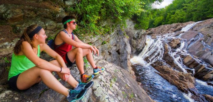 two older kid hikers look at a waterfall