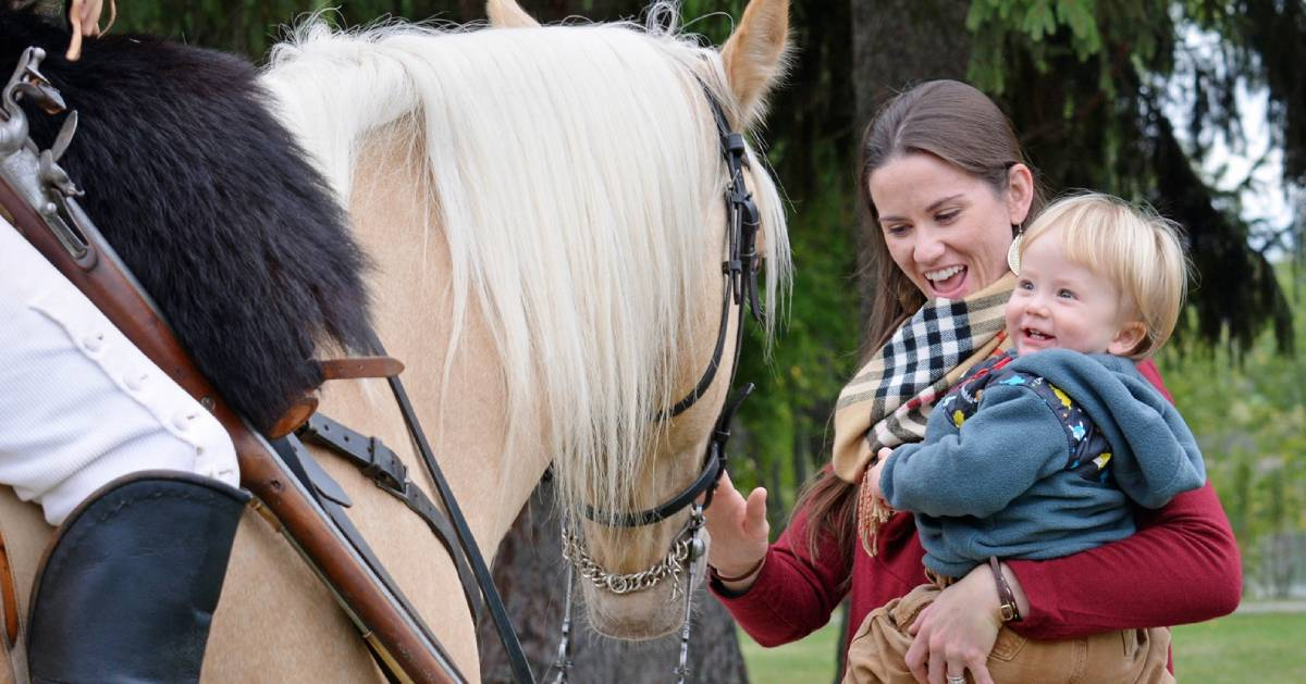 woman and toddler greeting horse