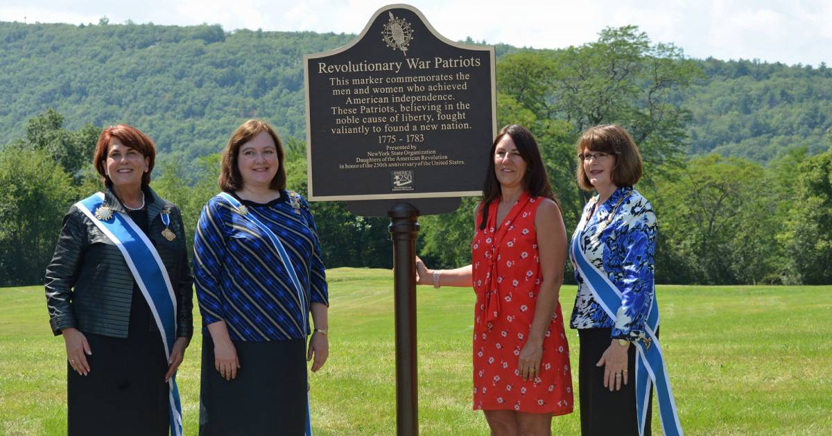 women standing next to a historical marker