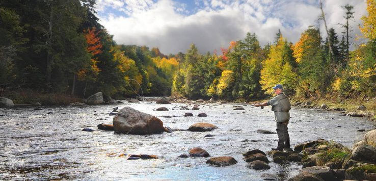 man fly fishing in the fall