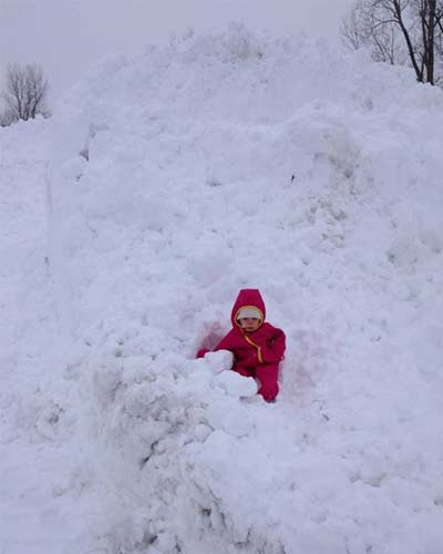 kid in snow pile