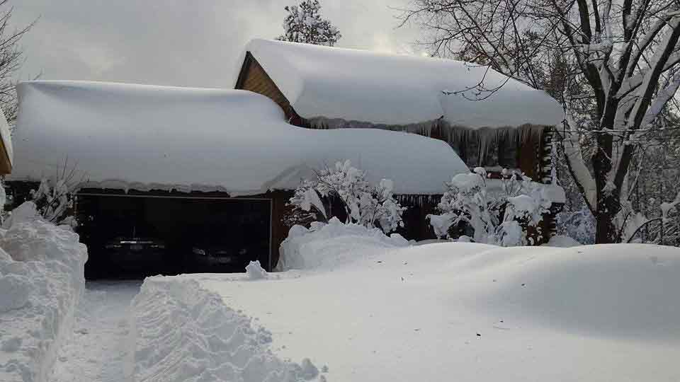 snow on top of a house and garage